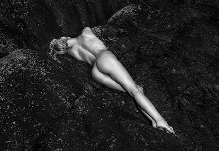 Model Mette Munkø Nude Lying with exposed arse on black rocks TH2013-1131. Foto/Photo: Thomas Holm